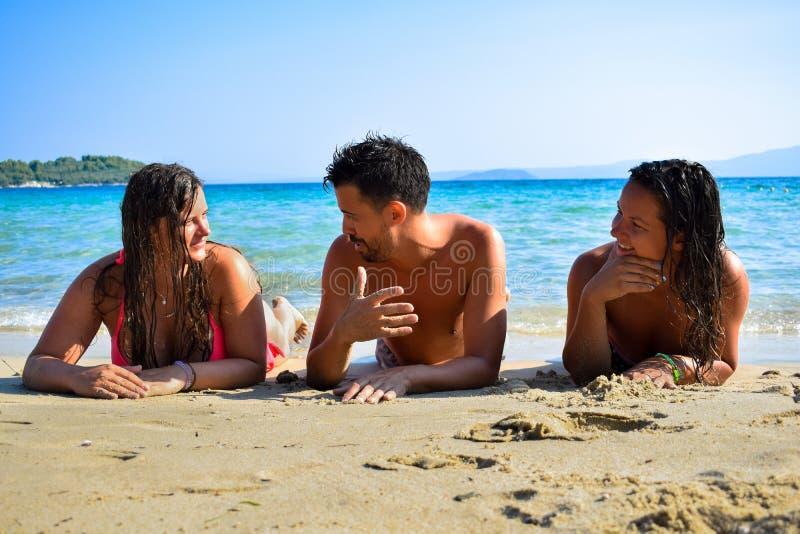 Vänner som meddelar, medan koppla av på stranden på havet arkivbilder
