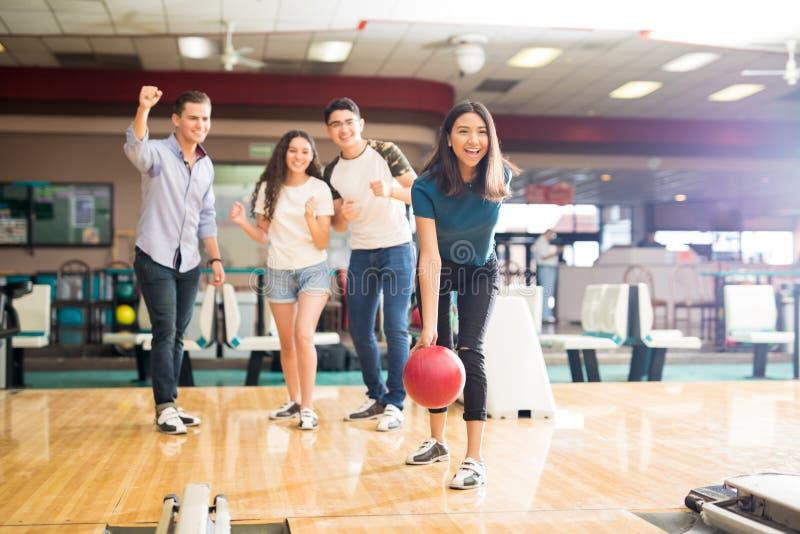 Vänner som motiverar den tonåriga flickan som kastar bowlingklot på gränden fotografering för bildbyråer