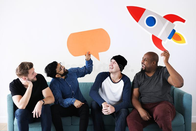 Vänner som placerar på soffan med anförandebubblan royaltyfri bild