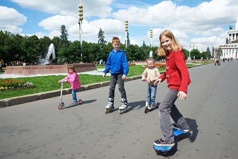 Vänner som rider en skateboard och en sparkcykel royaltyfri bild
