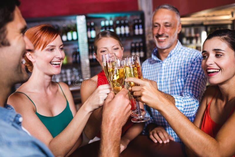 Vänner som rostar champagneexponeringsglas i nattklubb arkivbild