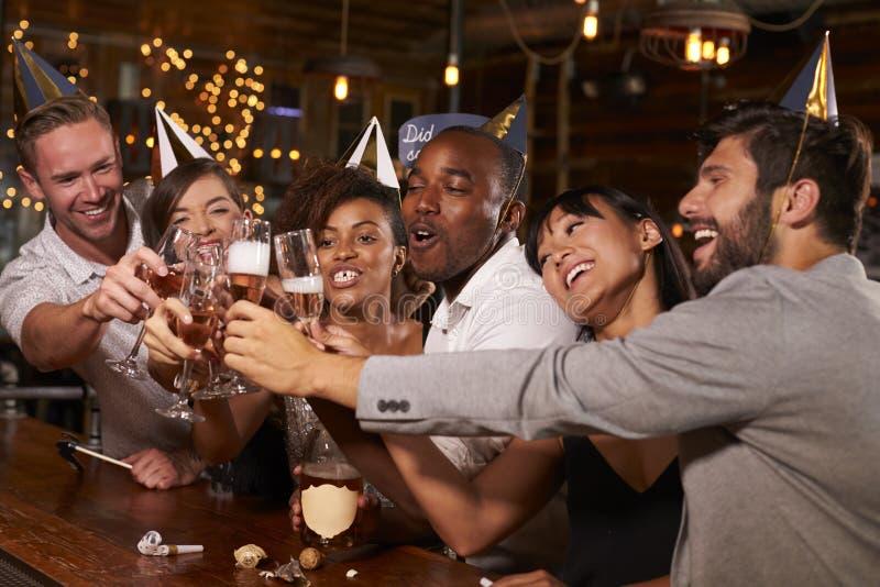 Vänner som rostar med champagne på det nya partiet för Yearï ¿ ½ s i en stång arkivbilder