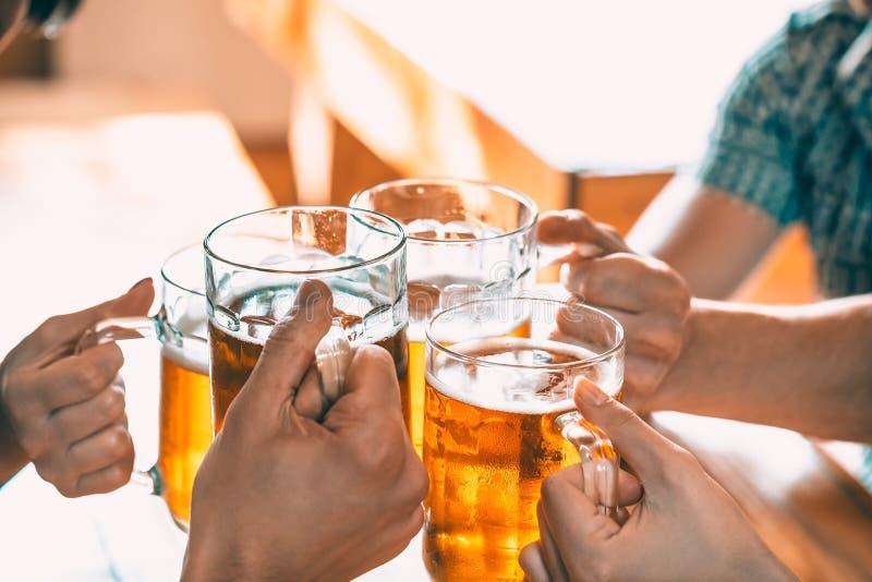Vänner som rostar med exponeringsglas av ljust öl på baren fotografering för bildbyråer