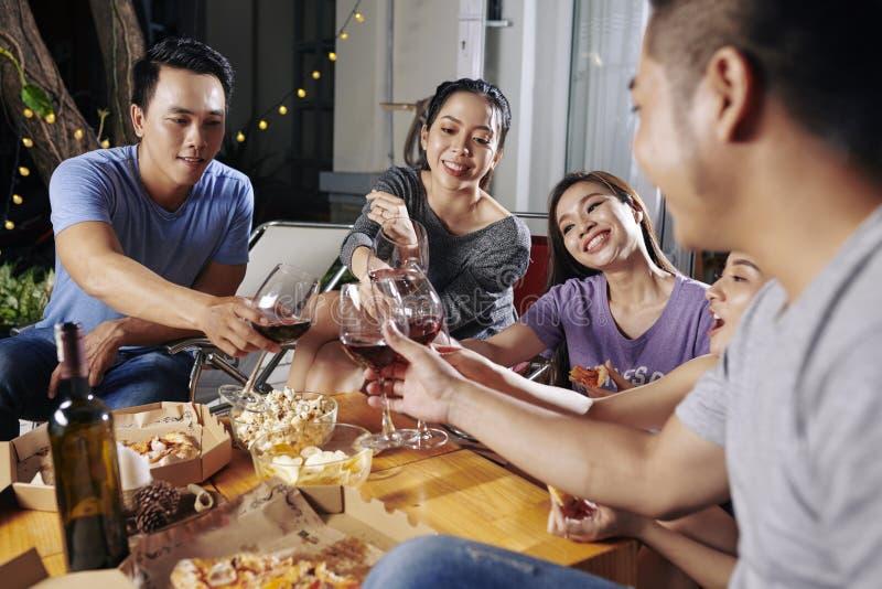 Vänner som rostar med vinexponeringsglas royaltyfri bild