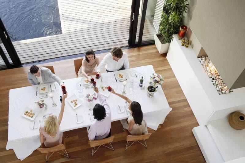 Vänner som rostar vin över tabellen på matställepartiet arkivfoto