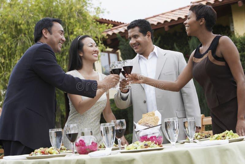 Vänner som rostar vin i matställeparti royaltyfri fotografi