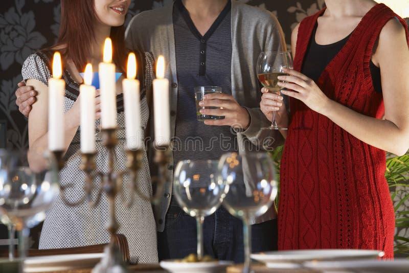 Vänner som rymmer drinkar, genom att äta middag tabellen royaltyfria foton