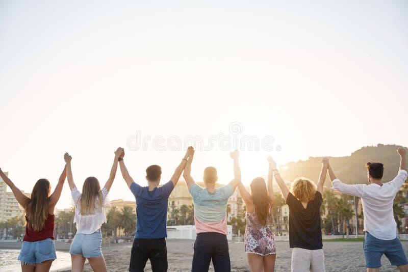 Vänner som rymmer upp händer tillsammans i segergest royaltyfri fotografi