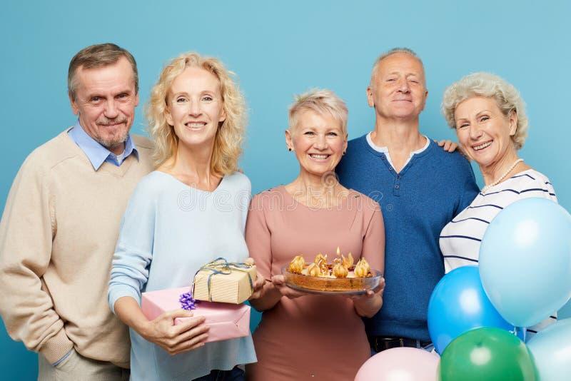 Vänner som samlar för födelsedagparti arkivbild