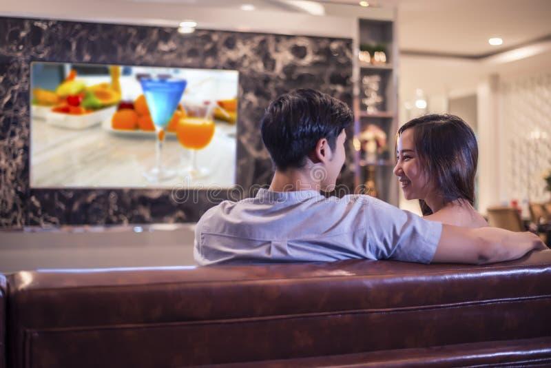 Vänner som ser de, medan hålla ögonen på television på soffan Koppla ihop och koppla av begreppet Nattbröllopsresatema, tillbaka  arkivfoton