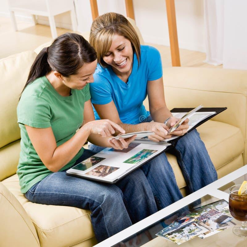 vänner som ser fotografier som sitter sofaen royaltyfri foto
