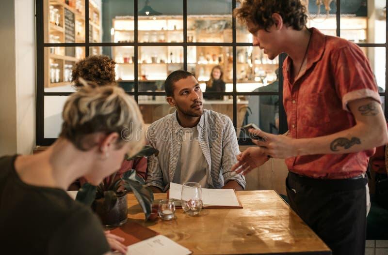 Vänner som sitter i en restaurang som beställer mat från en uppassare royaltyfria bilder