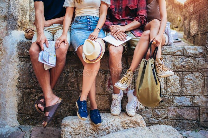 Vänner som sitter på det fria för en vägg med vår- och sommardresswear - - begrepp om kamratskap som är säsongsbetonat, livsstil, arkivbild