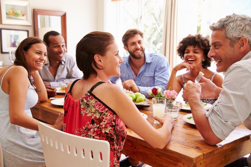Vänner som sitter på en tabell som talar under ett matställeparti royaltyfri foto