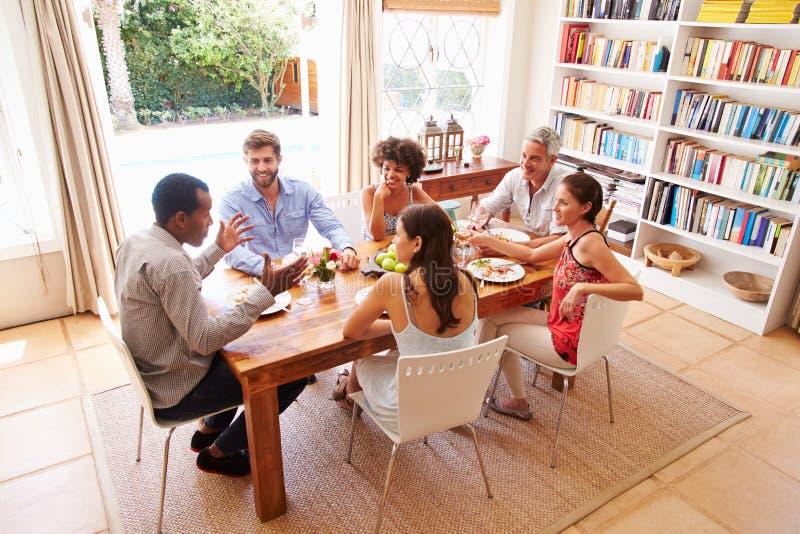 Vänner som sitter på en tabell som talar under ett matställeparti royaltyfri fotografi
