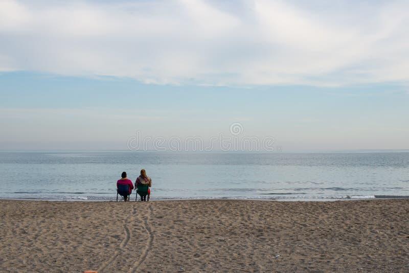 Vänner som sitter på kusten royaltyfria foton