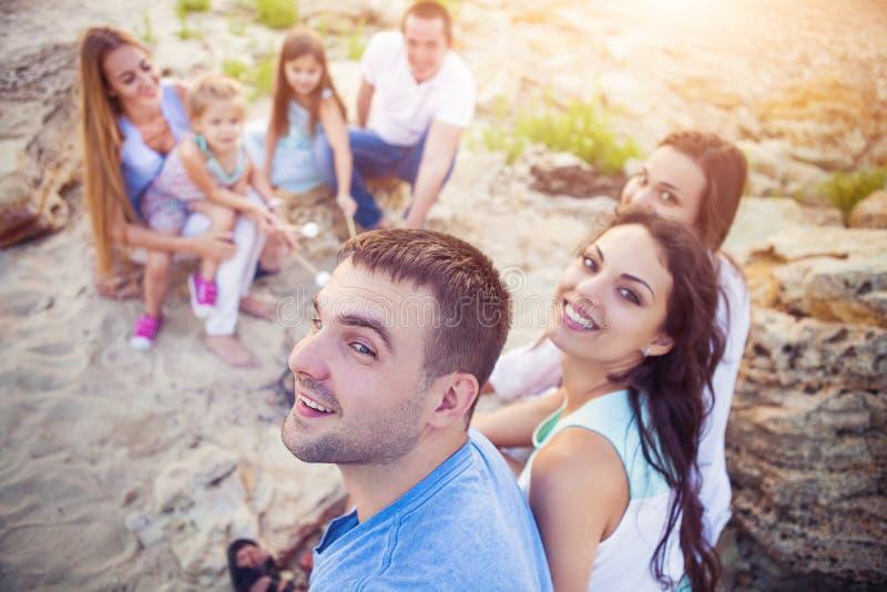Vänner som sitter på sanden på stranden i cirkel med marshmal royaltyfria foton