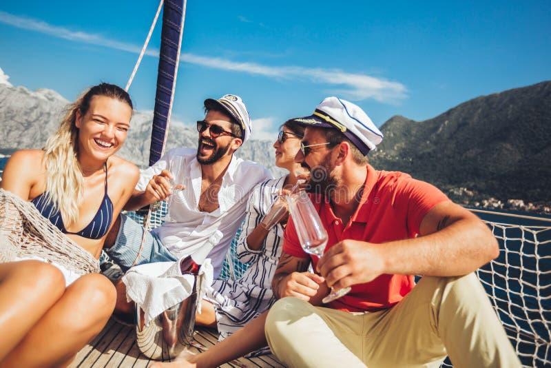 Vänner som sitter på segelbåtdäck och har gyckel Semester, lopp, hav, kamratskap och folkbegrepp arkivfoton