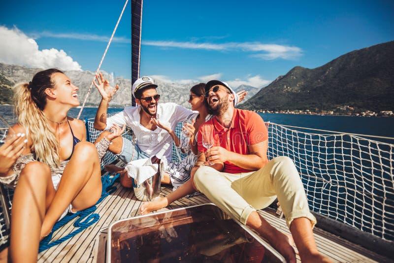 Vänner som sitter på segelbåtdäck och har gyckel Semester, lopp, hav, kamratskap och folkbegrepp arkivbilder