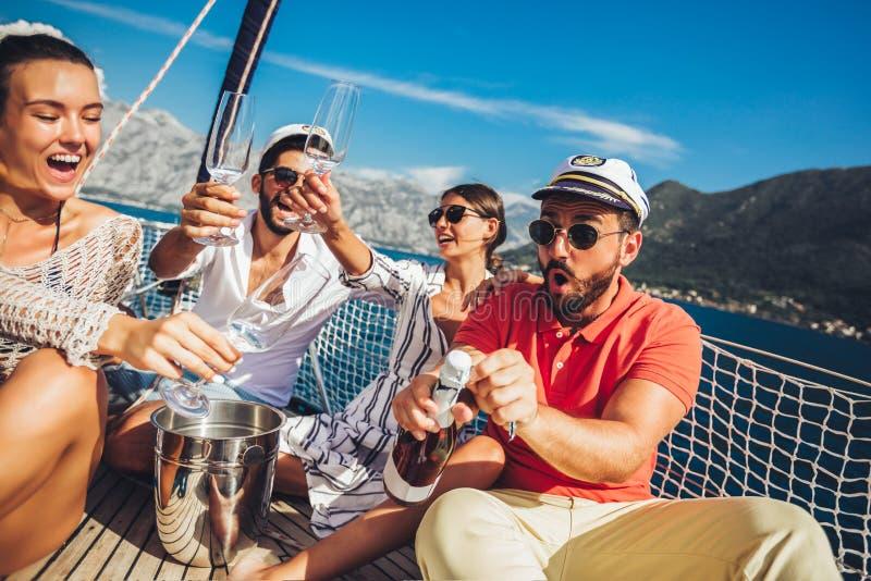 Vänner som sitter på segelbåtdäck och har gyckel Semester, lopp, hav, kamratskap och folkbegrepp arkivbild