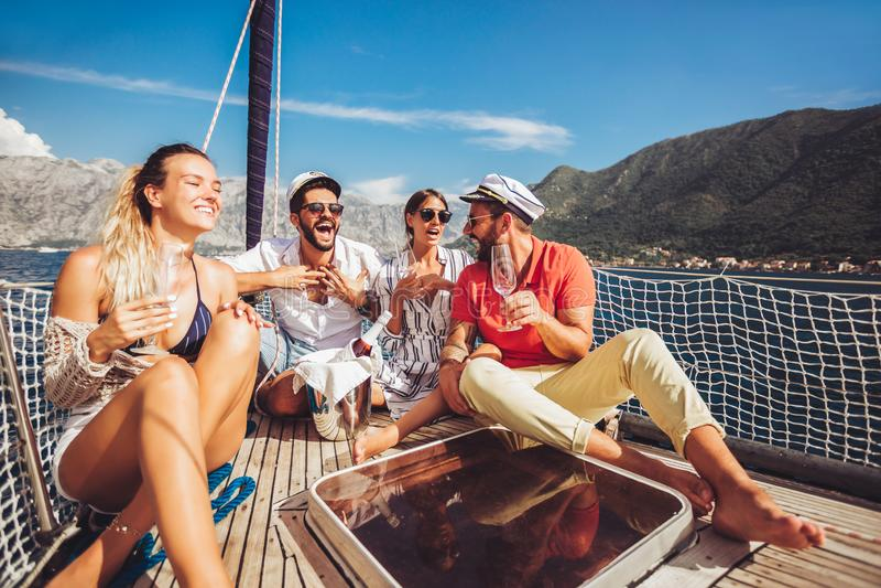 Vänner som sitter på segelbåtdäck och har gyckel Semester, lopp, hav, kamratskap och folkbegrepp royaltyfria bilder