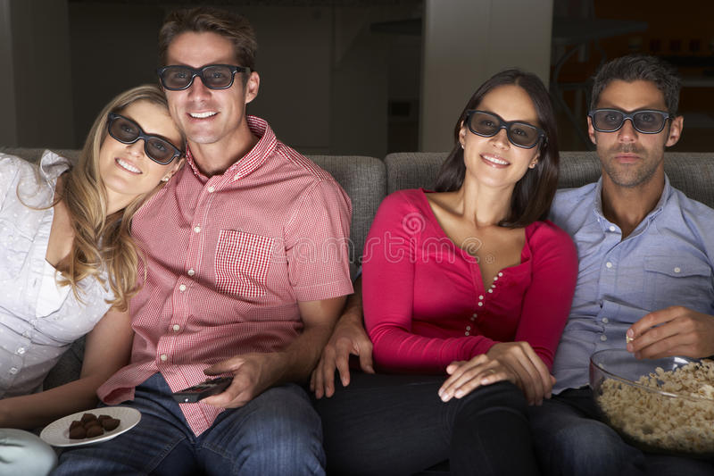 Vänner som sitter på Sofa Watching TV som bär 3-D exponeringsglas arkivbilder
