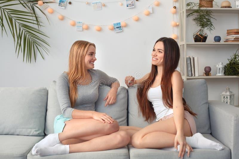 Vänner som sitter tillsammans hemma på glat soffasamtal royaltyfria bilder