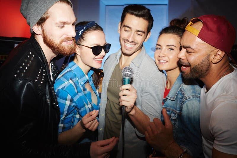 Vänner som sjunger karaoke i nattklubb royaltyfria bilder