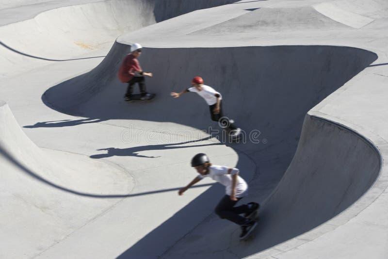 Vänner som in Skateboarding, parkerar royaltyfri bild