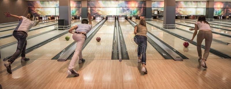 Vänner som spelar bowling arkivbilder