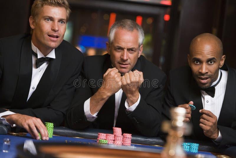 vänner som spelar den male rouletttabellen för grupp royaltyfri foto