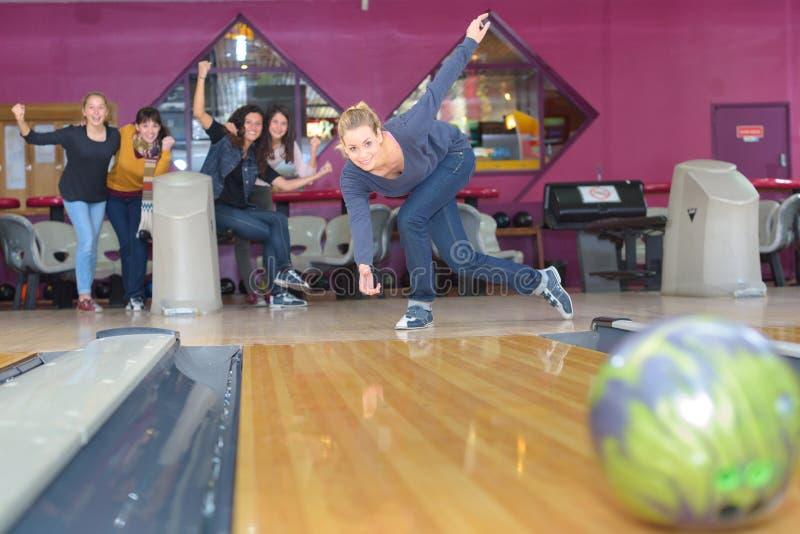 Vänner som spelar, i att bowla klubban royaltyfri foto