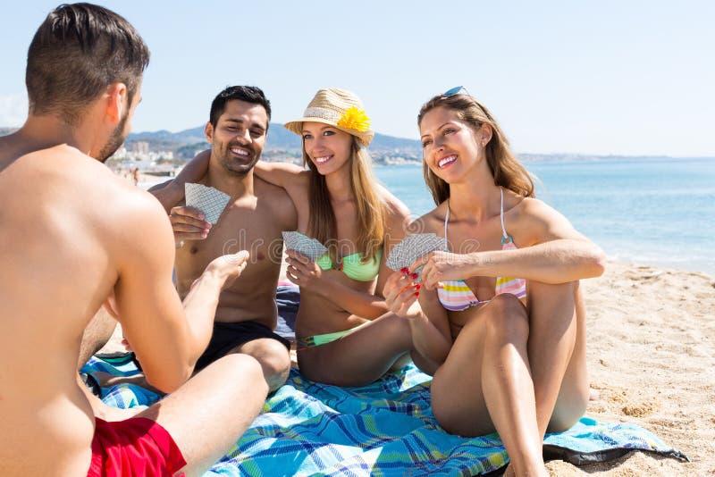 Vänner som spelar kort på stranden royaltyfri bild