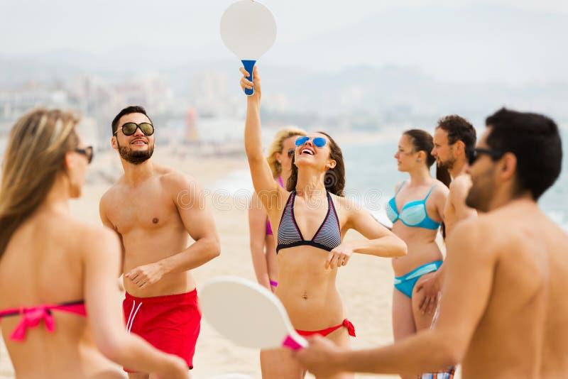 Vänner som spelar med racket på stranden royaltyfri bild