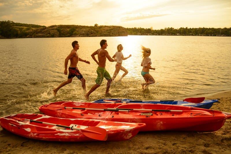 Vänner som spelar och har gyckel i vattnet på stranden nära kajaker under den dramatiska aftonhimlen på solnedgången arkivbilder