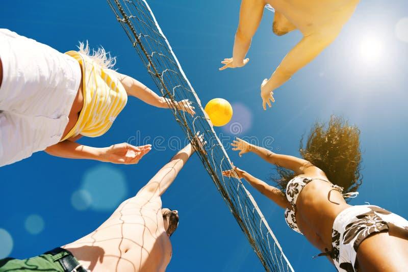 Vänner som spelar strandvolleyboll arkivfoto