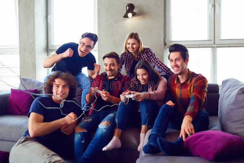 Vänner som spelar videospel i rummet arkivfoton