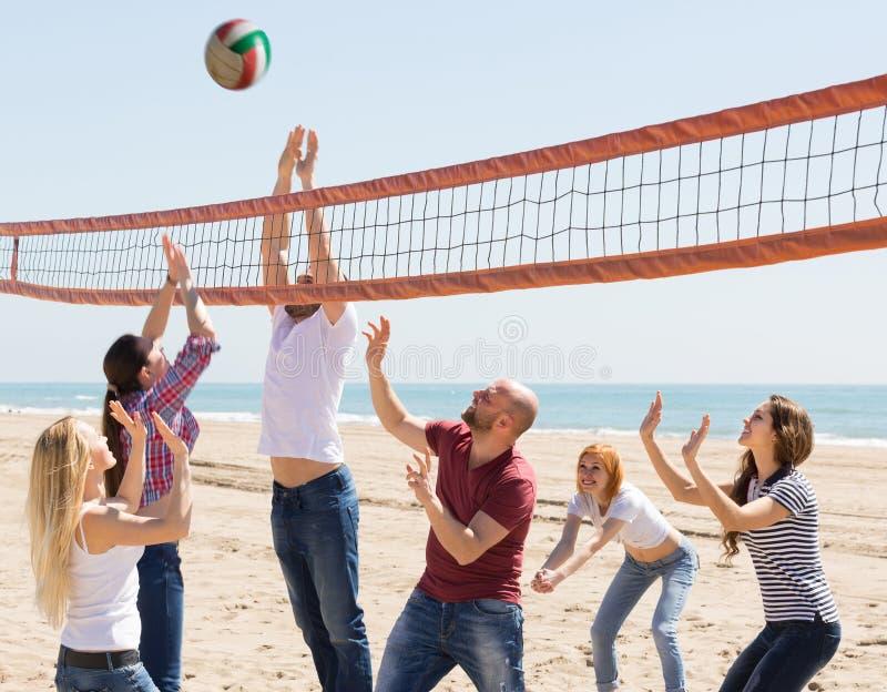 Vänner som spelar volleyboll på stranden royaltyfri fotografi