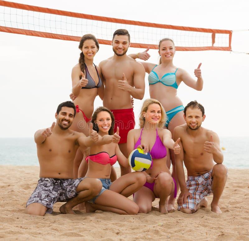 Vänner som spelar volleyboll på stranden arkivbilder