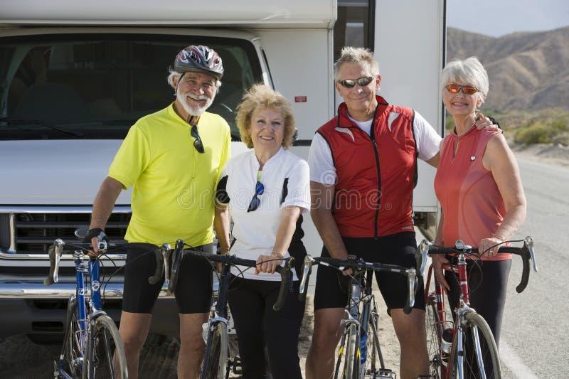 Vänner som står med cyklar med husvagnen i bakgrunden arkivbilder