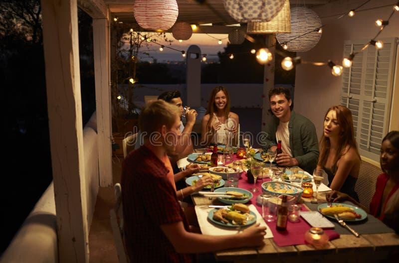Vänner som talar på ett matställeparti på en uteplats, Ibiza, Spanien arkivbild