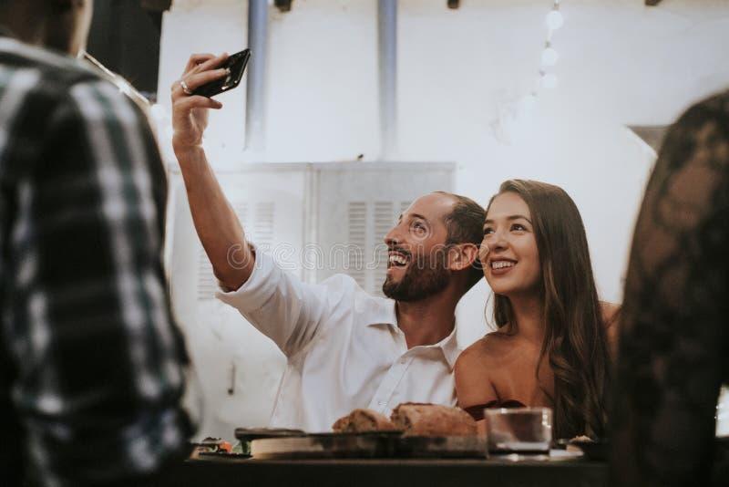 Vänner som tar en selfie på ett matställeparti royaltyfria bilder