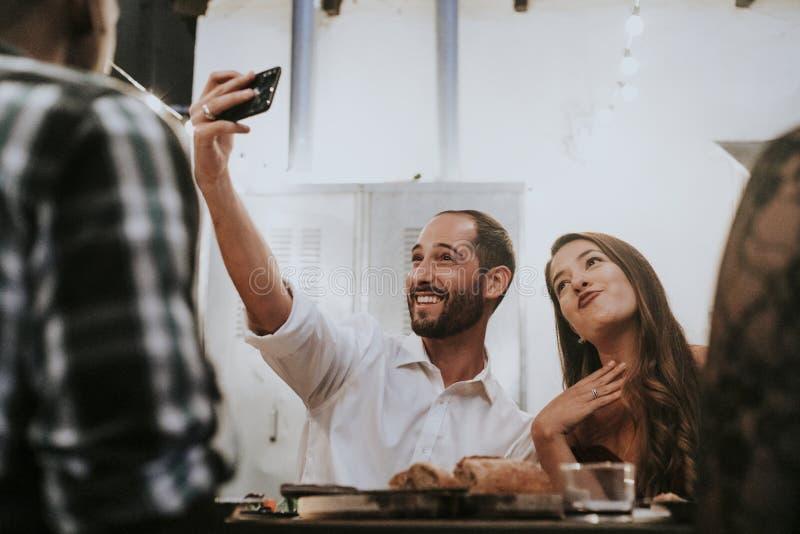 Vänner som tar en selfie på ett matställeparti fotografering för bildbyråer