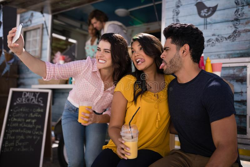 Vänner som tar selfie från mobiltelefonen i matlastbilskåpbil arkivfoton