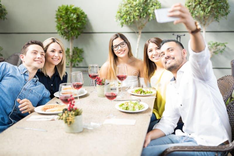 Vänner som tar selfie i en restaurang royaltyfri bild