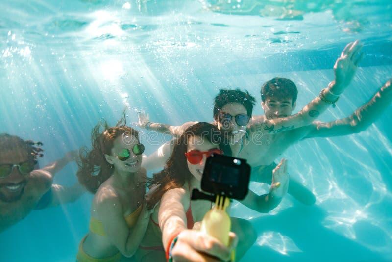 Vänner som tar selfie under vattnet i simbassäng fotografering för bildbyråer