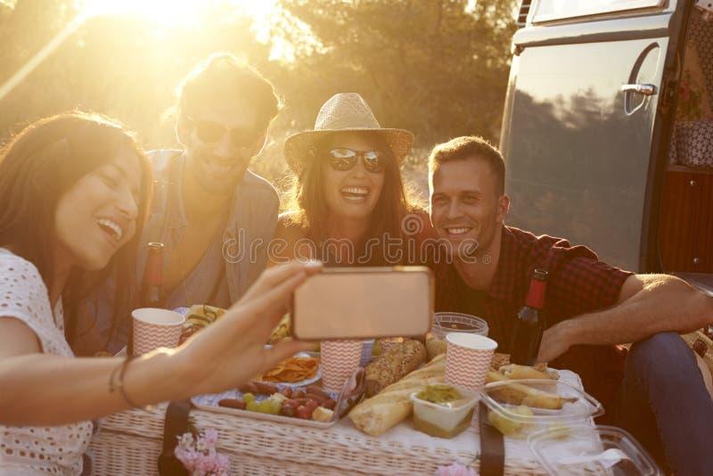 Vänner som tar upp selfie på picknicken bredvid campareskåpbilen, slut royaltyfri bild