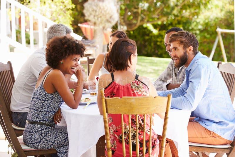 Vänner som tillsammans äter middag på en tabell i en trädgård arkivbild