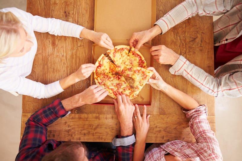 Vänner som tillsammans delar en pizza, över huvudet sikt royaltyfria foton