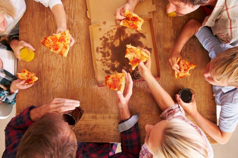 Vänner som tillsammans delar en pizza, över huvudet sikt royaltyfri bild